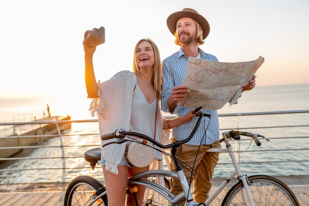 魅力的な幸せなカップルが自転車で夏に旅行、金髪の自由奔放に生きるヒップスタースタイルのファッションで一緒に楽しんで、カメラで写真を撮る地図観光で探している女性