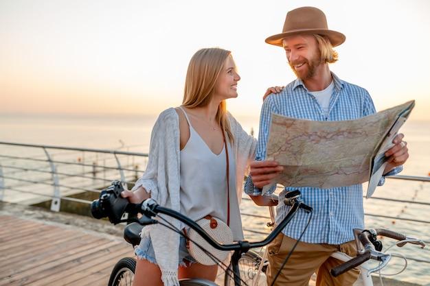 Привлекательная счастливая пара, путешествующая летом на велосипедах, мужчина и женщина со светлыми волосами в стиле хипстера в стиле бохо, весело проводящие время вместе, глядя на карту достопримечательностей