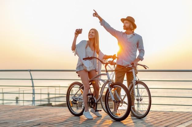魅力的な幸せなカップルが自転車で夏に旅行、ブロンドの自由奔放に生きるヒップスタースタイルのファッションで一緒に楽しんで、観光写真を撮る女性