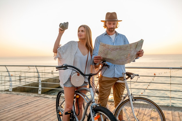 Attractive happy couple traveling in summer on bicycles, man and woman with blond hair boho hipster style fashion having fun together, looking in map sightseeing taking photos on camera
