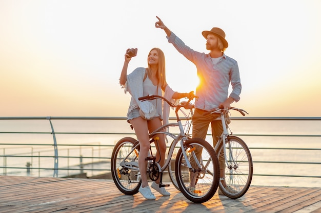 Attractive happy couple traveling in summer on bicycles, man and woman with blond hair boho hipster style fashion having fun together, taking photos sightseeing