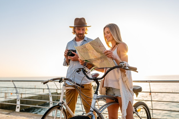 Attractive happy couple traveling in summer on bicycles, man and woman with blond hair boho hipster style fashion having fun together