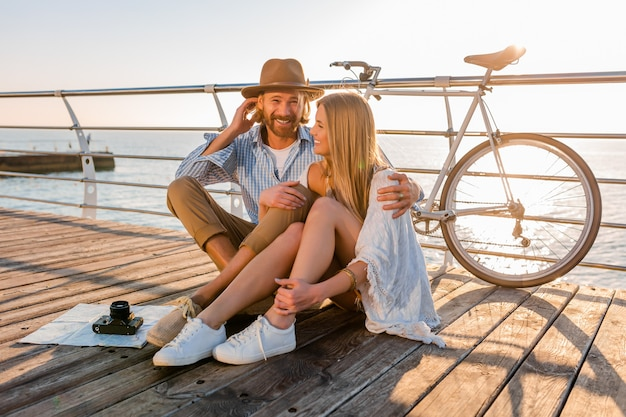 Attractive happy couple traveling in summer by sea on bicycles, man and woman boho hipster style fashion having fun together