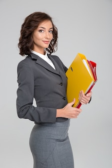 Attractive happy curly smiling confident business woman in gray costume holding colorful binders with documents