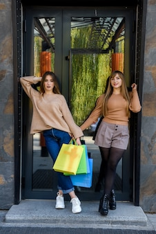 Attractive happy customers with packets after shopping posing outdoors