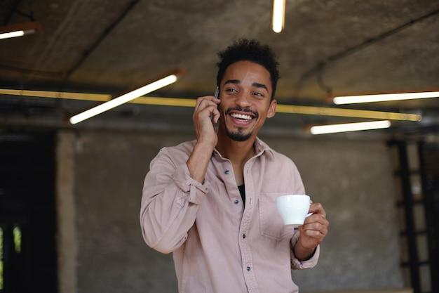 짧은 머리와 수염이 캐주얼 한 옷을 입고 현대적인 인테리어 위에 포즈를 취하고 커피를 마시고 친구에게 전화하여 재미있는 이야기를 들려주는 매력적인 행복 어두운 피부의 남자가 어제 일어났습니다.