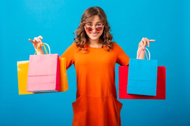 고립 된 블루 스튜디오 배경에 쇼핑 가방을 들고 오렌지 유행 특대 드레스에 매력적인 행복 정서적 웃는 세련된 여자 쇼핑 중독