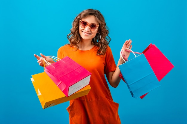 Attractive happy emotional smiling stylish woman shopaholic in orange trendy oversize dress holding shopping bags on blue studio background isolated
