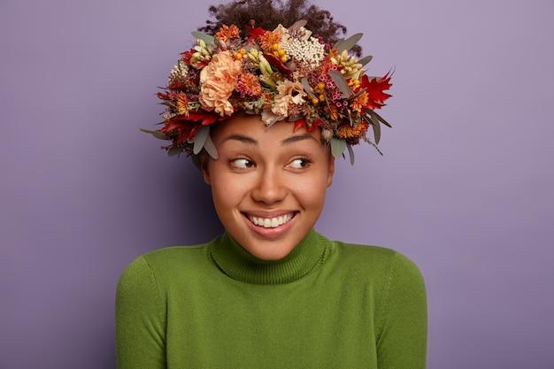 魅力的な幸せな女性は、自然の美しさを持ち、化粧をせず、秋の植物の花輪を身に着け、喜んで脇に見え、満足し、緑のタートルネックを身に着け、屋内でモデルを作ります。