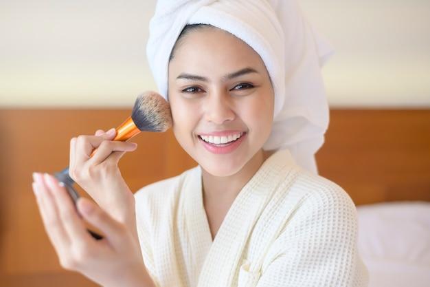 白いバスローブを着た魅力的な幸せな女性は、美容パウダーブラシ、ビューティーコンセプトでナチュラルメイクを適用しています。