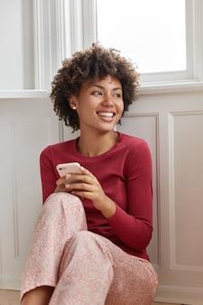아프로 헤어 스타일을 가진 매력적인 행복한 여성 모델은 잠옷을 입고 즐거운 문자 메시지를 읽고 긍정적으로 미소 짓고 바닥에 앉아 집에서 자유 시간을 보냅니다. 화려한 여자 친구 전화를 기다립니다.