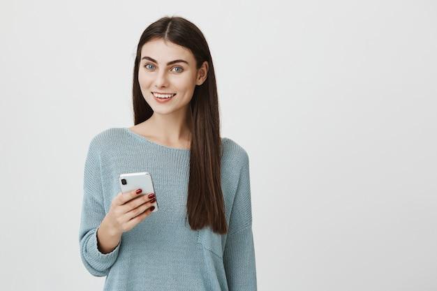 Привлекательная счастливая женщина улыбается с мобильным телефоном