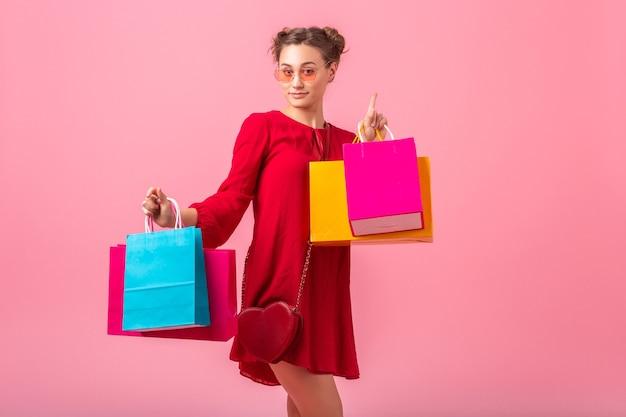 魅力的な幸せな面白い感情スタイリッシュな女性買い物中毒の赤い流行のドレスピンクの壁にカラフルなショッピングバッグを保持している孤立した、販売興奮、春夏のファッショントレンド