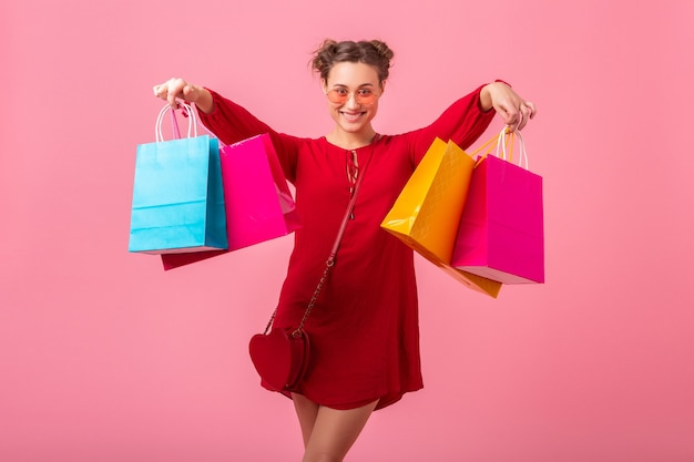 Привлекательные счастливые смешные эмоции стильная женщина-шопоголик в красном модном платье, держащая красочные сумки на розовой стене, изолированные, возбужденные продажи, весенне-летняя модная тенденция