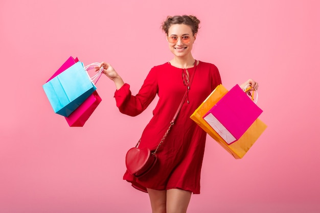 Attractive happy funny emotion stylish woman shopaholic in red trendy dress holding colorful shopping bags on pink wall isolated, sale excited, spring summer fashion trend