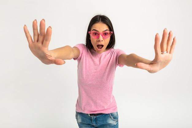 분홍색 티셔츠 고립 된 팔에 매력적인 행복 재미 감정적 인 여자 앞으로 놀란 얼굴의 충격 식