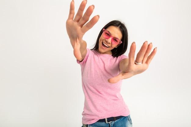 Привлекательная счастливая смешная эмоциональная женщина в розовой футболке изолировала руки вперед