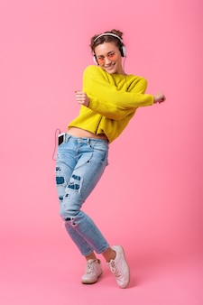 Attractive happy funny woman dancing listening to music in headphones dressed in hipster colorful style outfit isolated on pink studio background