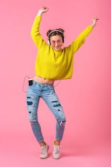 ピンクの壁に分離されたヒップスターのカラフルなスタイルの服を着て、黄色のセーターとサングラスを身に着けて、楽しんでヘッドフォンで音楽を聴いて踊る魅力的な幸せな面白い女性
