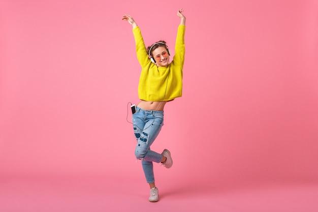 ピンクの壁に分離された流行に敏感なカラフルなスタイルの衣装に身を包んだヘッドフォンで音楽を聴いて踊る黄色いセーターの魅力的な幸せなおかしい女性、楽しんで