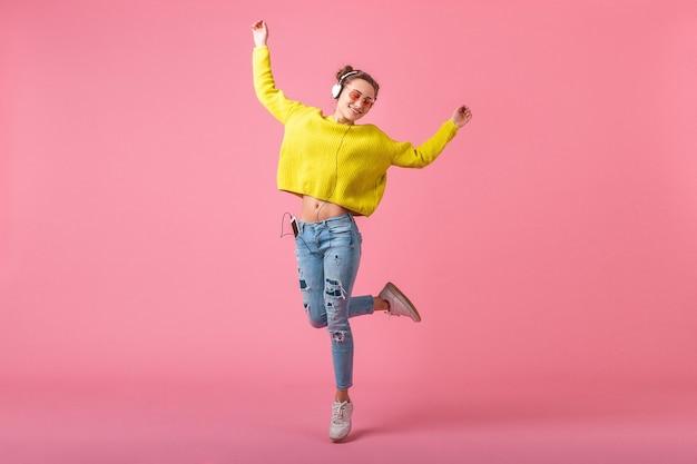 Привлекательная счастливая смешная женщина в желтом свитере прыгает, слушая музыку в наушниках, одетая в красочный хипстерский наряд, изолированный на розовой стене, весело