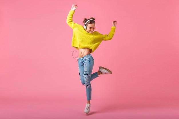 Привлекательная счастливая смешная женщина прыгает, слушая музыку в наушниках, одетая в красочный стиль хипстера, изолированного на розовой стене, в желтом свитере и солнцезащитных очках, веселится
