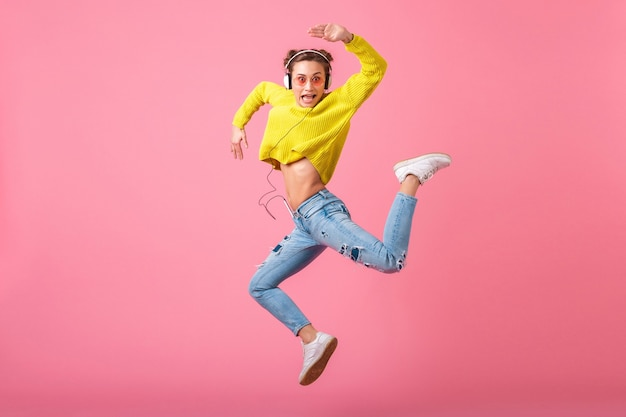 매력적인 행복 재미 있은 여자 점프, 노란색 스웨터와 선글라스를 착용, 재미, 분홍색 벽에 고립 힙 스터 화려한 스타일의 옷을 입고 헤드폰에서 음악을 듣고