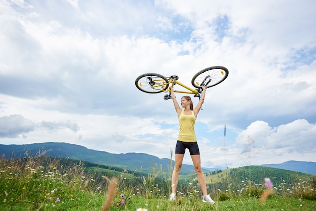 Attractive happy girl cyclist holding yellow mountain bike above a head