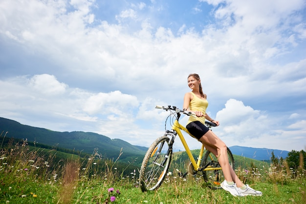 Attractive happy girl cyclist sitting on yellow mountain bike, enjoying summer day in the mountains