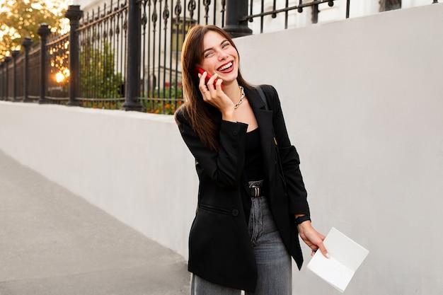 携帯電話で話し、笑っている魅力的な幸せな女の子。