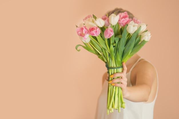 花の花束を持つ魅力的な幸せな女の子