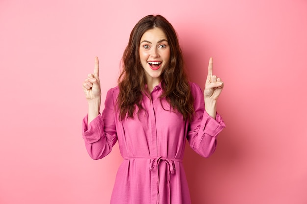 Attractive happy lady pointing fingers up and smiling cheerful, showing awesome advertisement, standing over pink wall.