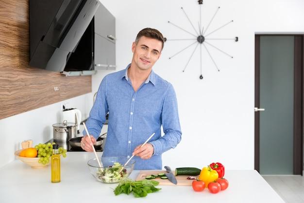 青いシャツを着た魅力的な幸せな男が立って、台所でベジタリアン サラダを作る