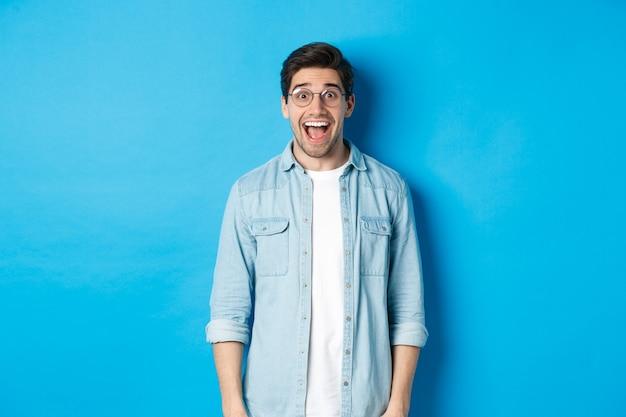 Привлекательный счастливый человек в очках, глядя удивлен, проверяя рекламу, стоя на синем фоне.