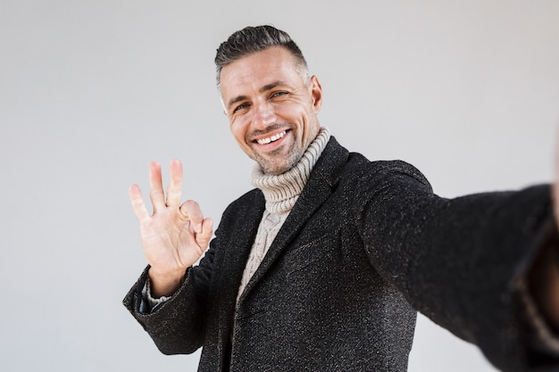 Attractive happy man wearing coat standing isolated over gray wall, taking a selfie, showing ok