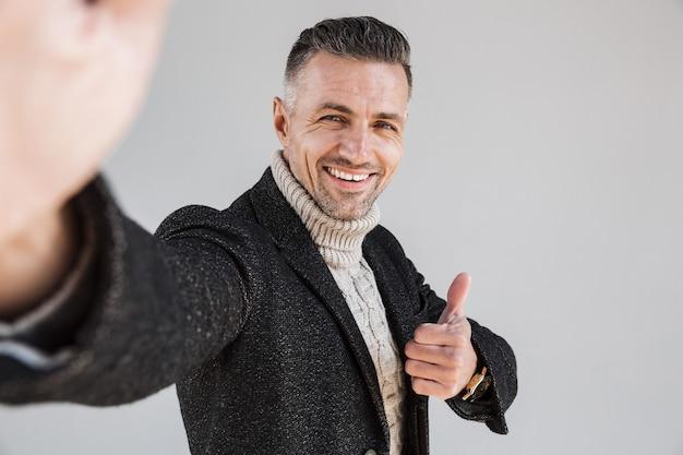 灰色の壁の上に孤立して立っているコートを着て、自分撮りを取り、親指をあきらめる魅力的な幸せな男