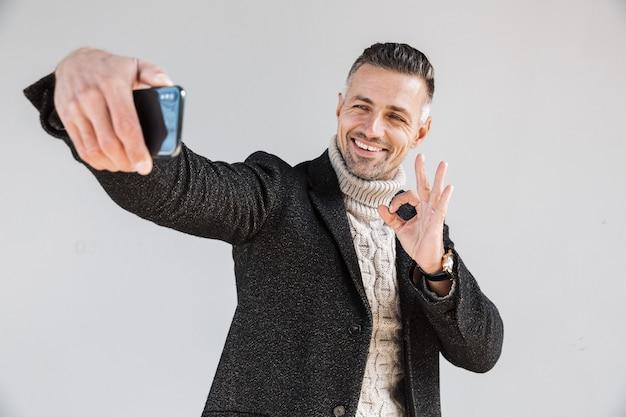 灰色の壁の上に孤立して立っているコートを着て、自分撮りをして、大丈夫を示している魅力的な幸せな男