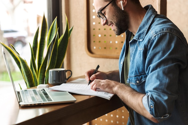 Attractive happy man wearing glasses writing and using earpod with laptop while working in cafe indoors