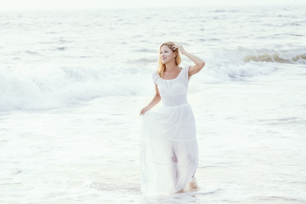 Attractive happy mature tourist blonde woman in long white dress on asian sand tropical beach.