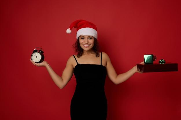 이브닝 드레스와 산타 모자를 쓴 매력적인 혼혈 여성, 카메라를 보며 미소 짓는 미소, 손에 알람 시계와 크리스마스 선물을 들고 빨간색 배경, 복사 공간