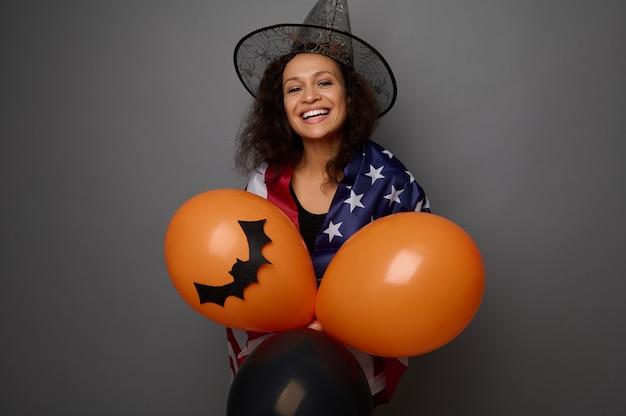 アメリカの国旗に包まれた魔法使いの帽子をかぶった魅力的な幸せな混血の女性は、カラフルなオレンジ色の空気球を保持し、カメラを見て歯を見せる笑顔を浮かべます。コピースペースと灰色の背景にハロウィーンのコンセプト
