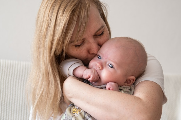 작은 아기를 껴 안은 매력적인 해피 어머니. 행복한 가족. 집에서. 사랑. 단. 유연함.