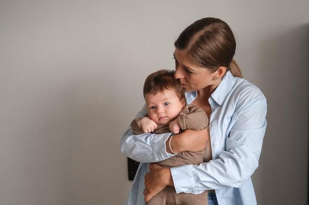 웃는 아기 소녀를 들고 매력적인 해피 어머니 키스. 간호 아기. 행복한 가족. 집에서. 사랑. 단. 유연함. 함께 보내는 시간을 즐겨보세요. 고품질 사진 프리미엄 사진