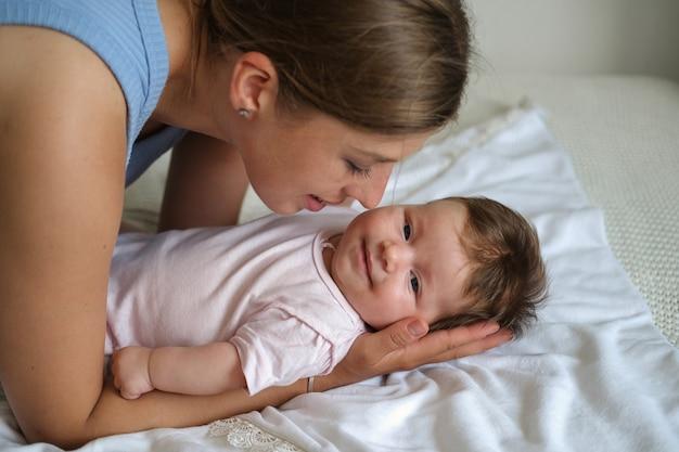작은 웃는 아기 소녀와 함께 누워 매력적인 해피 어머니 키스. 행복한 가족. 집에서. 사랑. 단. 유연함. 고품질 사진
