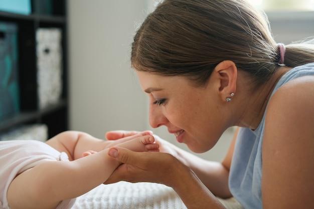 매력적인 해피 어머니는 작은 아기 소녀 발가락을 킁킁 키스. 잠자는 아이. 엄마 간호 아기. 행복한 가족. 집에서. 사랑. 단. 유연함. 함께 시간을 즐기십시오.