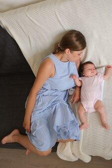 소파에 작은 아기와 함께 누워 매력적인 행복 한 어머니. 평면도. 행복한 가족. 집에서. 사랑. 단. 유연함. 고품질 사진