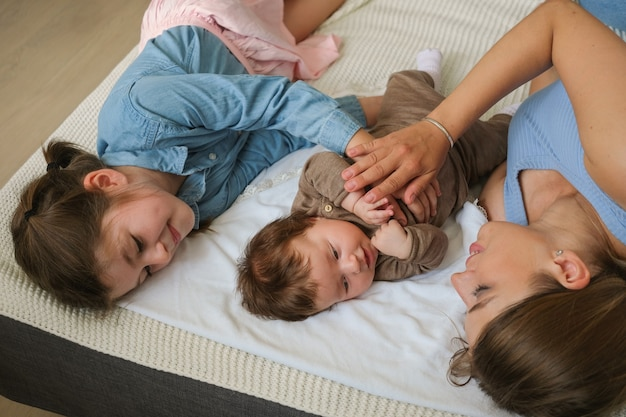 Attractive happy mother lying with two daugther. little baby girl on couch. top view. happy family. at home. love. sweet. tenderness. big sister.