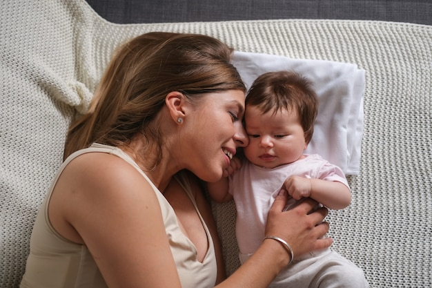 Attractive happy mother play with little toes baby girls. mom nursing baby. face to face. happy family. at home. love. sweet. tenderness.