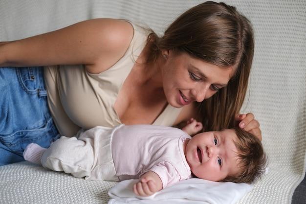 Привлекательная счастливая мать играет с маленькими пальчиками девочек. мама грудного ребенка. счастливая семья. дома. любовь. милая. нежность.