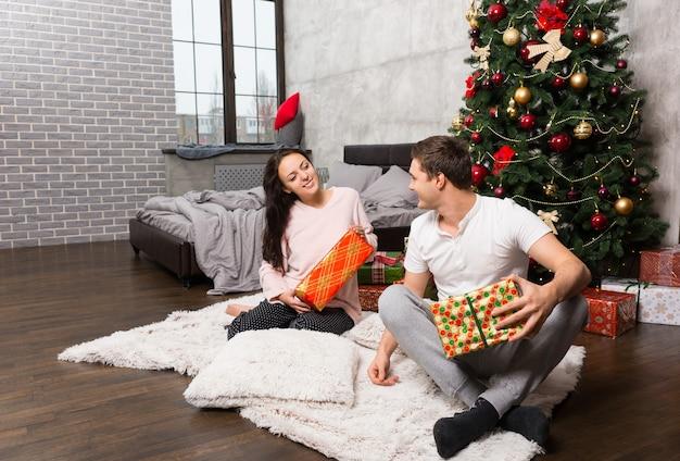 ロフトスタイルの部屋のクリスマスツリーの近くのカーペットに座っている間、パジャマの魅力的な幸せなペアは彼らのプレゼントを喜ぶ
